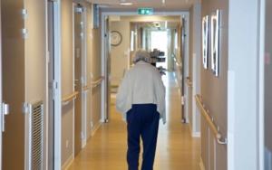 Senior living home with woman walking through thr hall